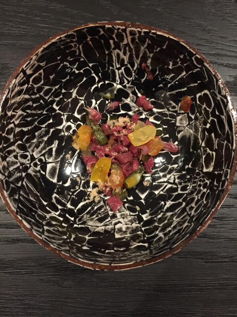 Tatar vom Rinderherz, Schnittlauchblüte, gebeizten Saibling, selbst eingelegten Essiggurken, salzig eingelegter Löwenzahn und gebeiztes Eigelb, fein gerieben.